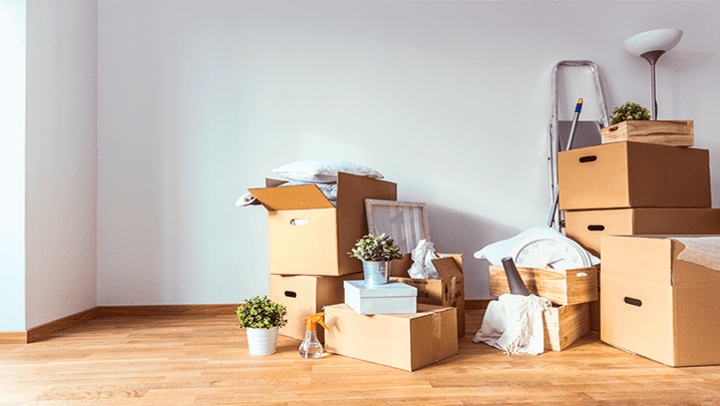 Cardboard boxes stacked in a living room.