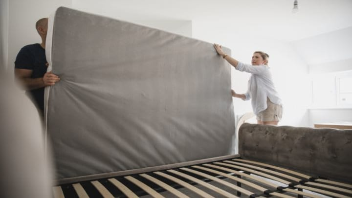 A couple putting a mattress on a bed frame.