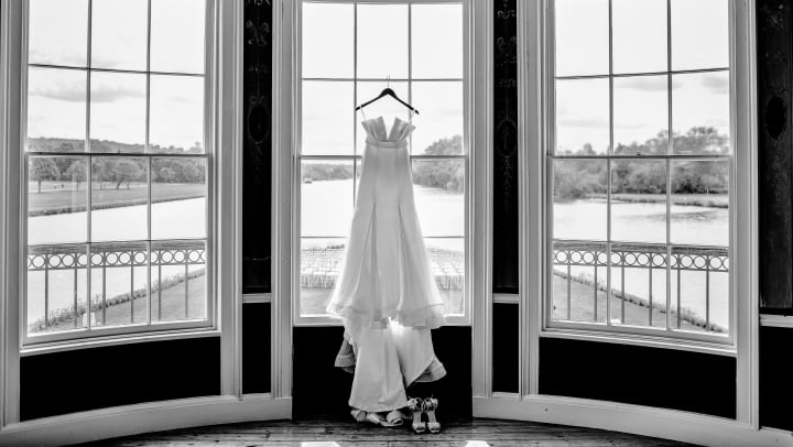 A wedding dress hanging in front of three large bay windows.
