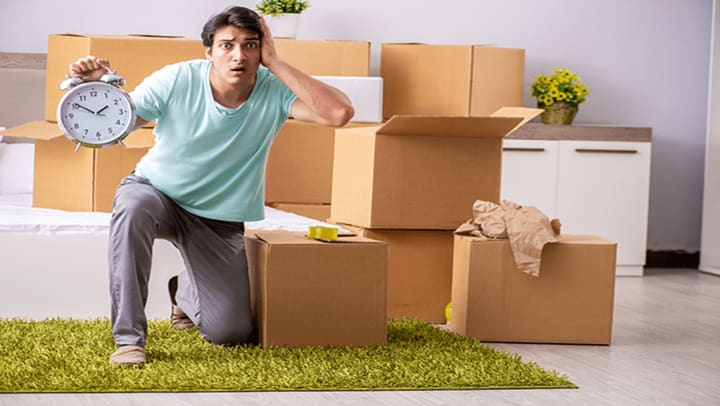 A confused man holding a clock surrounded by moving boxes.