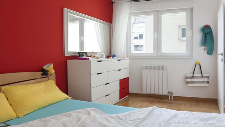 A red and white bedroom with a dresser.