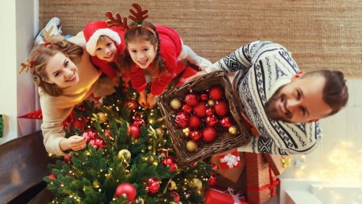 A couple and their two children decorating a Christmas tree with red and gold ornaments.